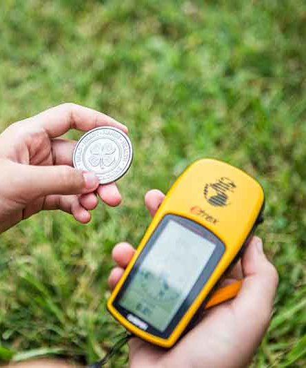 child holding a 4-H coin and a Garmin GPS navigator