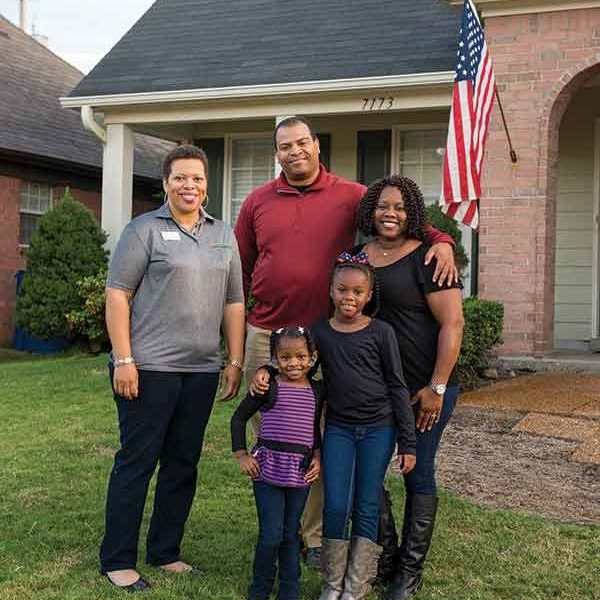 Family posing in front of their first home